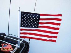 harley davidson motorcycle with 1 motorcycle flagpole with usa flag mounted on the luggage rack.