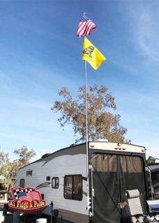 RV toy hauler with ramp flagpole mount, 22' telescopic flagpole, usa and do not tread on me (gadsden) flags. Flags blowing in the wind with blue skies,